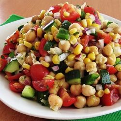 Corn and Chickpea Fiesta Salad A cold salad of chickpeas, corn, cherry tomatoes, cucumbers, green pepper, and red onion with a cilantro-lime dressing.