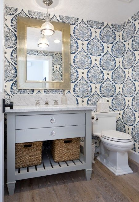 Champagne gold beveled mirror is mounted on a wall covered in Galbraith & Paul Lotus Wallpaper above a light gray single washstand fitted with a shelf holding woven bins and a Carrera marble top with a sink and a polished nickel faucet lit by a Jamie Young St.