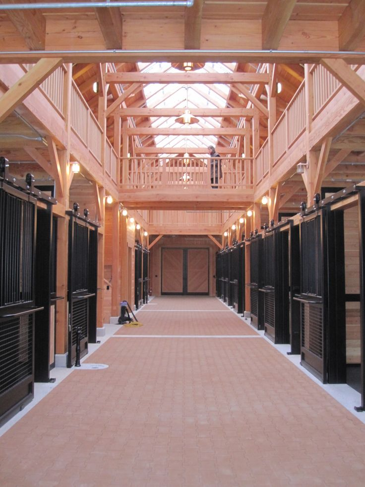 luxury horse barns with courtyard | Main aisle of the barn with the hayloft bridge visible. Uses a large ...
