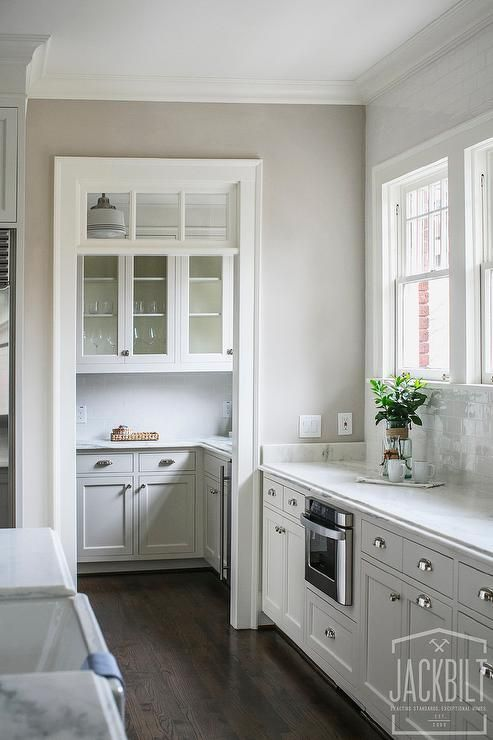 Beautiful kitchen features white cabinets paired with white marble countertops and a white subway tiled backsplash.