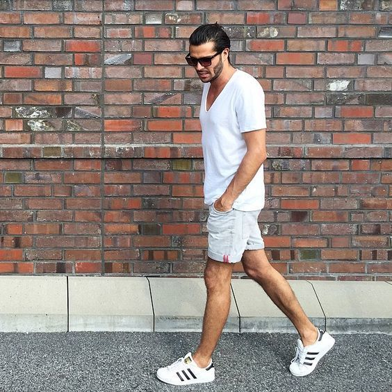 Den Look kaufen: https://lookastic.de/herrenmode/wie-kombinieren/t-shirt-mit-v-ausschnitt-weisses-shorts-weisse-niedrige-sneakers-weisse/20255   — Dunkelbraune Sonnenbrille  — Weißes T-Shirt mit V-Ausschnitt  — Weiße Jeansshorts  — Weiße Niedrige Sneakers