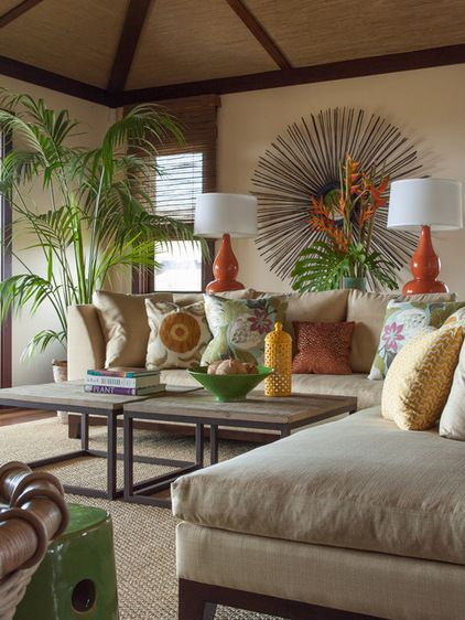 An elegant Hawaiian home furnished with neutral decor is the perfect spot for a tall Kentia palm, which creates a connection to the lush landscaping outdoors. Orange and yellow pillows and decorative accessories create a joyful dance of color together with the philodendron leaf arrangement and the feather-like green palm fronds.