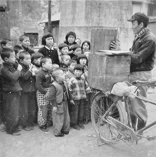 Children being told a story in the street by a kamishibai story teller. These storytellers would travel around with the kamishibai on the back of their bicycles, as they were relatively light and easy to transport.