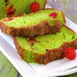 Pistachio Bread-1 (18.25 ounce) package yellow cake mix  4 eggs  1/4 cup vegetable oil  2 tablespoons water  1 (3 ounce) package instant pistachio pudding mix  1 cup sour cream  1/2 cup maraschino cherries  1/2 teaspoon green food coloring  1/2 teaspoon ground cinnamon  2 tablespoons white sugar