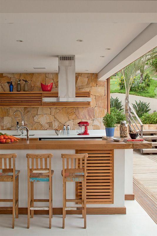 A parede da área gourmet recebeu placas grossas de arenito nas cores amarelo e rosa, fornecidas, assentadas e impermeabilizadas pela Margrape. Batedeira da KitchenAid e garrafas da Loja do Teo.