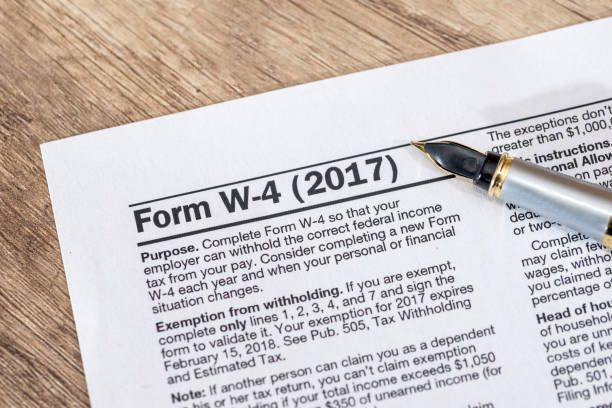 w 4 tax form with pen on desk
