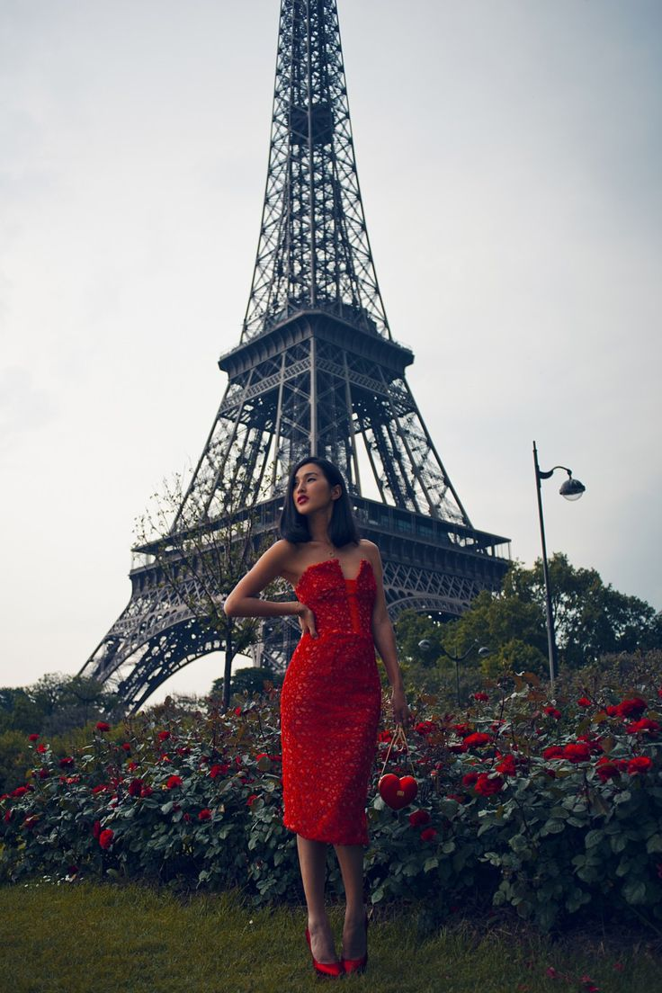 Nicole Warne in front of the Eiffel Tower in a Manning Cartell strapless red dress, Moschino heart bag, Gorjana necklace, Jennifer Zeuner bracelet, Charlotte Olympia heels, and Lancome Rouge in Love Red Lipstick in 170N.