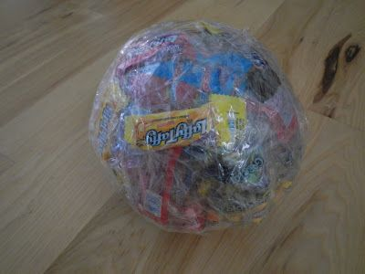 The idea is to use saran wrap & tape to create a ball. As you continue to wrap you add a piece of candy to each layer. Have the kids sit in a circle. Just like musical chairs, play music and the ball is passed around. When the music stops, the person holding the ball has till the count of 5 to unwrap as much candy as they can. Wrap a bell in the center and as you get closer you can hear the bell ring.