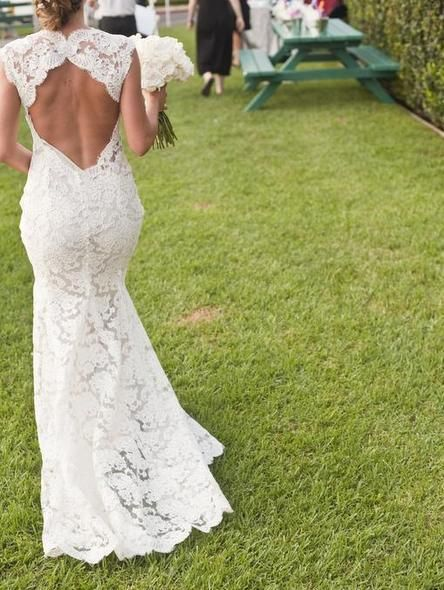 A daring back adds a little drama to this classic lace wedding dress
