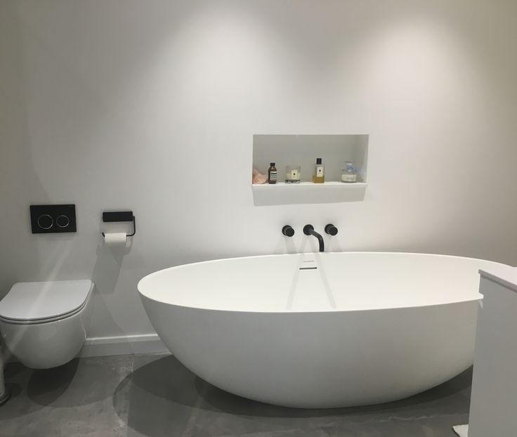 Minimal grey bathroom with matt black features and a freestanding bath