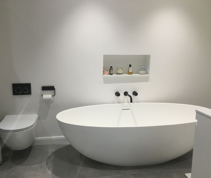 Minimal grey bathroom with matt black features and a freestanding bath