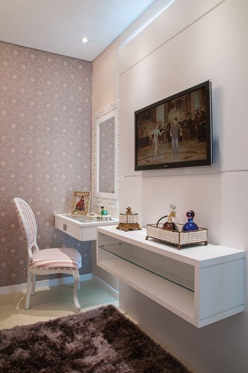 Ao lado da TV, a designer projetou um espaço que recebeu uma penteadeira, acompanhada por uma poltrona em madeira estofada com estampa compondo com o papel de parede. No hall que dá acesso ao quarto, o roupeiro com portas em espelho garante amplitude à entrada.