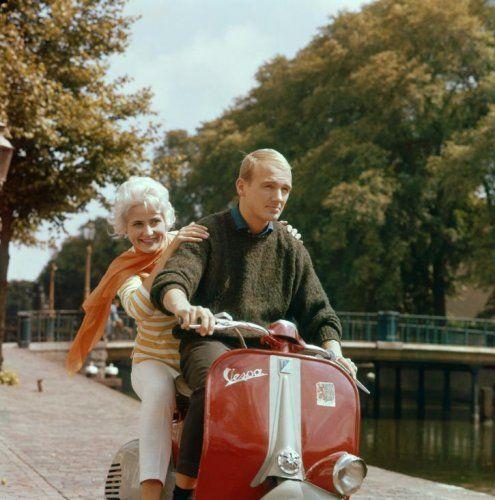 Vervoer, scooters. Een jongeman en een geblondeerd meisje [mogelijk zijn vriendin] met een oranje sjaal rijden op een rode Vespa scooter langs de Nieuwe Gracht in Haarlem. De bomen langs de gracht beginnen al herfsttinten te vertonen. Op de voorkant van de Vespa een sticker met het wapen van de provincie Noord-Holland. Zonder datum [omstreeks 1960].
