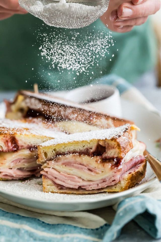 An easy Monte Cristo Sandwich recipe layered with ham, turkey, and Swiss, then battered and fried in the oven. Dust with powdered sugar for the ultimate breakfast sandwich! My favorite Monte Cristo Sa