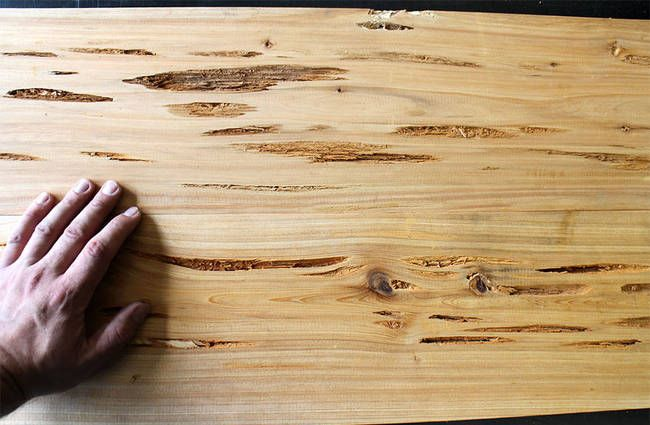 It starts out with Pecky cypress wood. A board of it has naturally occurring depressions and holes that are perfect for the design of the table.
