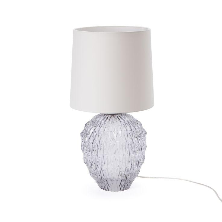 Unere Tischleuchte Horlev ist ein opulenter Blickfang. Mundgeblasenes Glas setzen das Hauptaugenmerk auf den geschwundenen Lampenfuß, während der Baumwollschirm den Raum in sanftes Licht taucht.