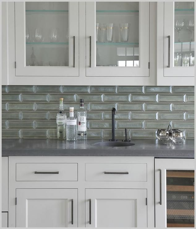 SSS Design & Interiors - White shaker butler's pantry cabinets accented with oil rubbed bronze pulls and a gray quartz countertops are fitted with a glass front wine cooler.