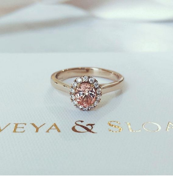 Naveya & Sloane bespoke oval shaped peach sapphire centre stone, with a claw set diamond halo. Crafted in 18k rose gold.
