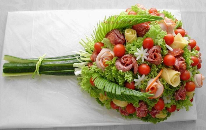 This is so pretty... It looks like a head of hydro lettuce placed on the display plate, and the ham roses, tomatoes (I assume with toothpicks pokes underneath to keep in place), swiss cheese rose and other flora placed into the lettuce to make it look like a bunch of flowers.