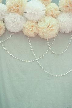 Photobooth backdrop of tissue pompoms and paper hole-punch streamers.