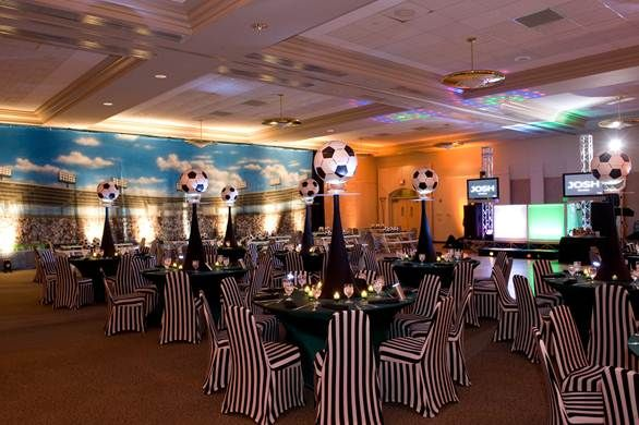 Soccer centerpiece with black white striped chair covers and wall mural