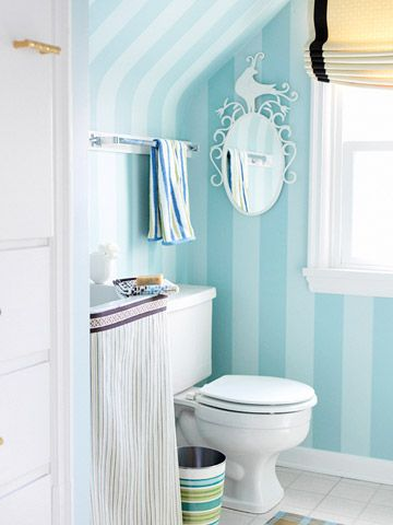 The large-scale striped wallpaper is an invigorating background in the tiny bath. There wasn't room for a standard mirror above the sink because of the angle of the walls, so the fanciful peacock mirror is mounted on a side wall. (the before picture is crazy)