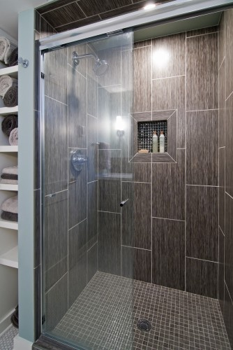 tile placed vertically on wall that matches bathroom floor shower floor in mosaic tile that