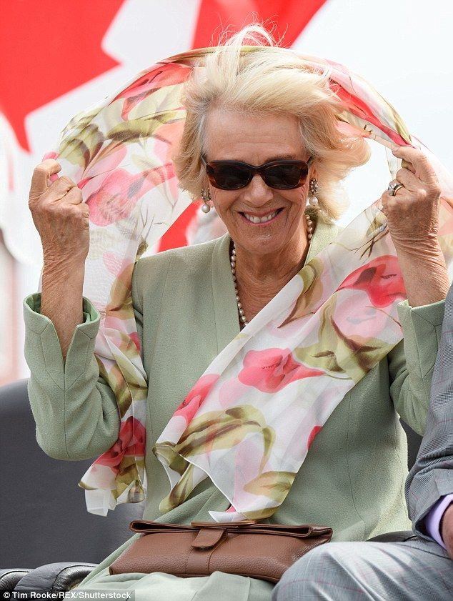 Seeing the funny side: Camilla struggled to keep hold of her floral scarf as it billowed in the wind, with their Canada tour getting off to a colourful start on Thursday