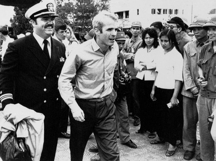 """John S. McCain III being escorted to Hanoi's Gia Lam Airport to head back to the United States. McCain, who was often referred to as the """"crown prince"""" by his captors for his father's position in the US Navy, spent five and a half years as a POW, much of that time in solitary confinement. He was shot down 26 October 1967 and was released 14 March 1973.    I definitely recommend this article which McCain wrote in May 1973. I think it is one of the most telling considering h"""