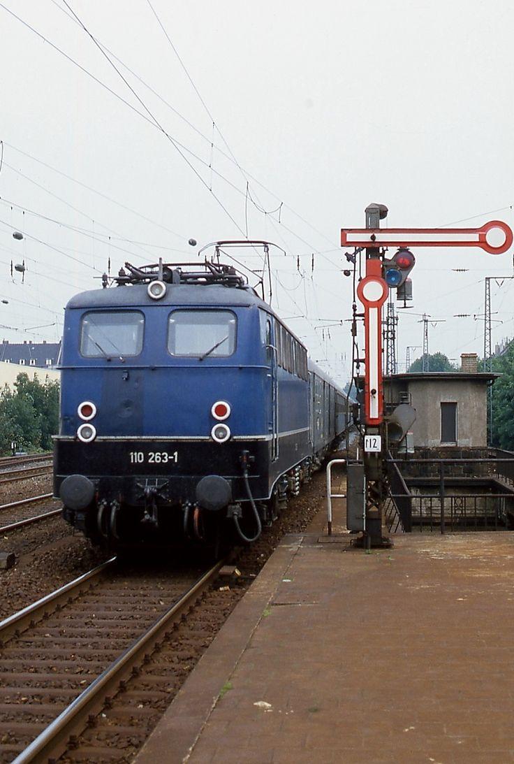 Um 1980 fährt 110 263-1 mit einem Eilzug in den Bahnhof Düsseldorf-Bilk ein. Im Zusammenhang mit dem Bau der Ost-West-S-Bahn wurden der Bahnhof und die Brücke, über die der Zug gerade fährt, umgebaut. Dabei verschwand leider auch das schöne Ausfahrtsignal.