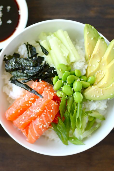 Sushi rice bowl with fresh salmon, nori, cucumber, avocado, edamame, and green onions.