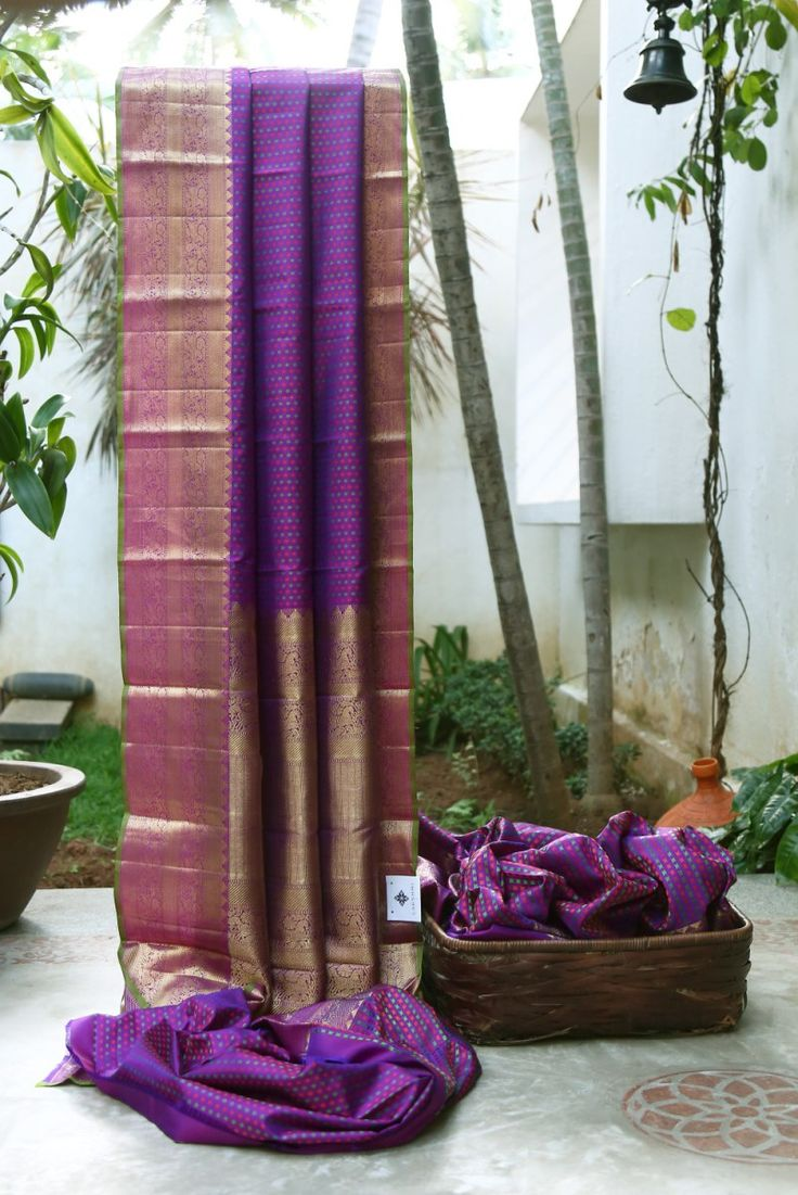 FETCHING VIOLET IRDESCENT MAGENTA WITH DOTTED RED AND GREEN ALL OVER HAS INTRICATELY WOVEN GOLD BORDER AND PALLU GIVING THE SAREE RADIANT FINISH.