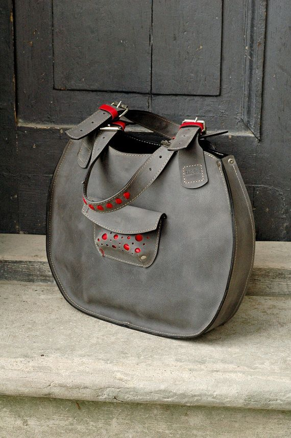 Adorable, edgy, comfortable Luci bag handcrafted in our leather craft studio will enhance any outfit and will make you stand out from the crowd.  Product description:  Height: 30 cm  Width: 42 cm  Straps length: 62 cm max.  Weight: about 1,4 kg  Pockets size: 33 cm / 22 cm  Size: fits A4 paper  Production lead time: 3 to 15 business days  A big city bag Lusi is handcrafted from natural leather in Grey color with Red leather detailing. Natural leather as a natural material has marks and…