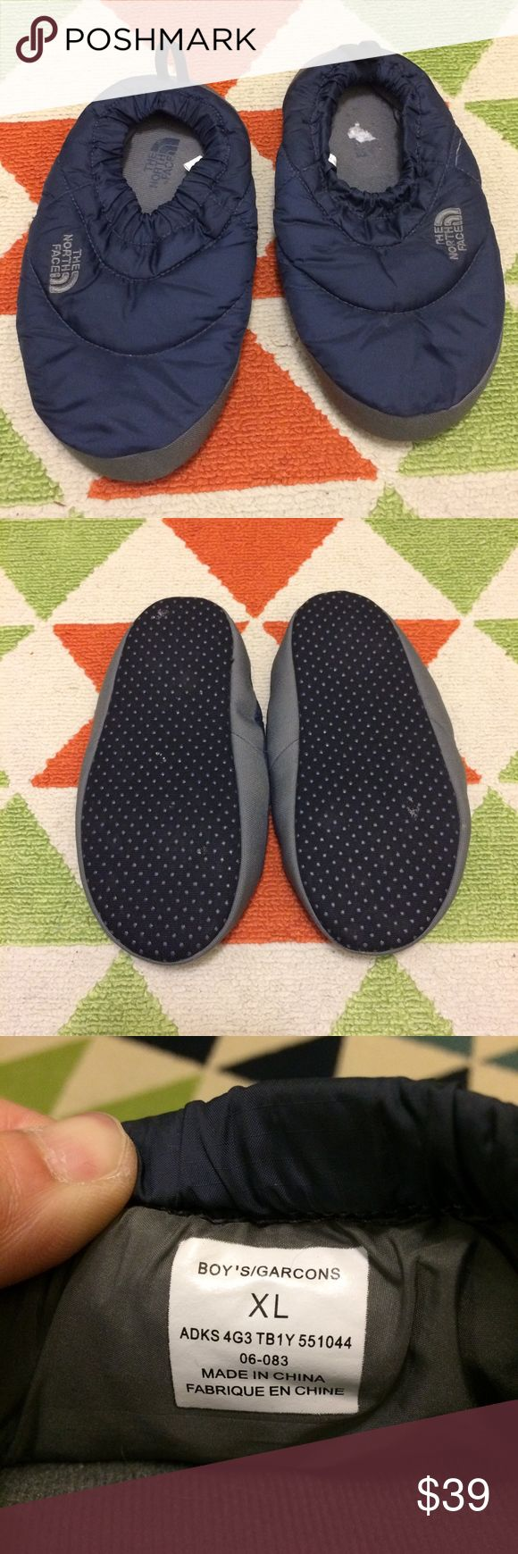 The North Face Down Slippers Excellent condition! Navy with grey trim, down slippers, grippy dots on the soles, pull tabs, and elastic opening. These say Boys XL and I am a womens size 8, these fit a bit snug but still fit. So I would say if you're a womens size 7 or 6 these would be perfect for you. The inside sole has the price sticker parts which I will continue to remove but thats all! The North Face Shoes Slippers