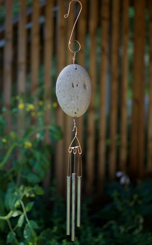 A beautiful beach stone wind chime- inspired by nature. The sweet sounding chimes are cut from raw brass and treated with a reactive-- the finish is not paint: it will not flake or peel. The chimes me