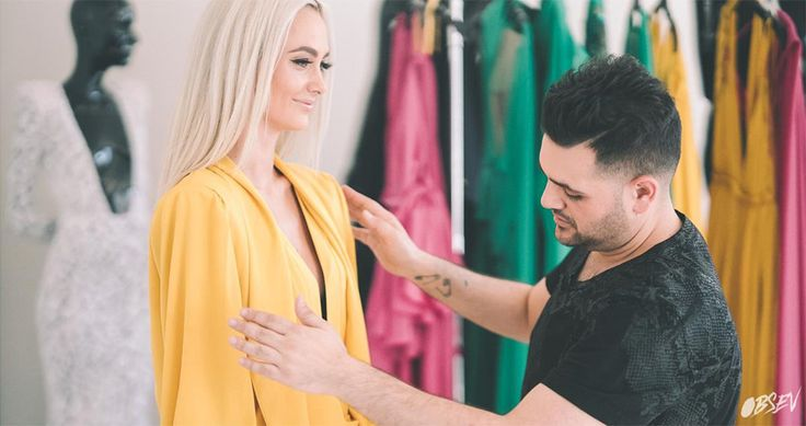 Designer Michael Costello fits a model into her perfect cape.