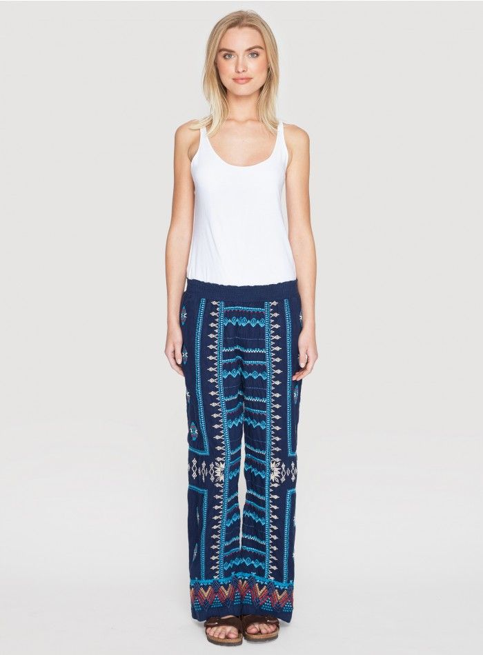 Sunniva Linen Palazzo Pant The JWLA SUNNIVA PALAZZO PANT will be a unique addition to your wardrobe! These wide-leg palazzo pants feature an all-over embroidery design in bold turquoise and white hues on navy blue linen. Pair these linen palazzo pants with an oversized silk blouse, wide-brimmed hat, and espadrilles for a resort-ready look!  - Navy Blue Linen - Shirred Elastic Waist, Wide Legs - Signature Embroidery - Care Instructions: Machine Wash Cold, Hang Dry
