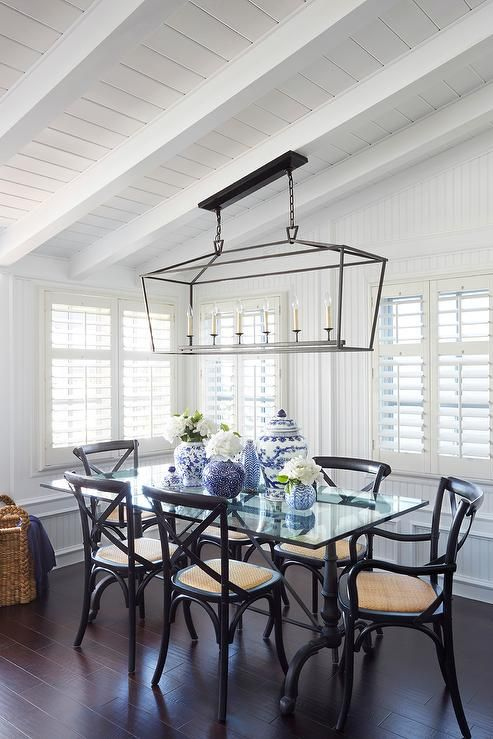 Absolutely gorgeous dining room features a sloped shiplap ceiling adorned with white wood beams accented with a Darlana Linear Pendant illuminating a black French dining table with glass top lined with black x back dining chairs surrounded by walls clad in beadboard trim.