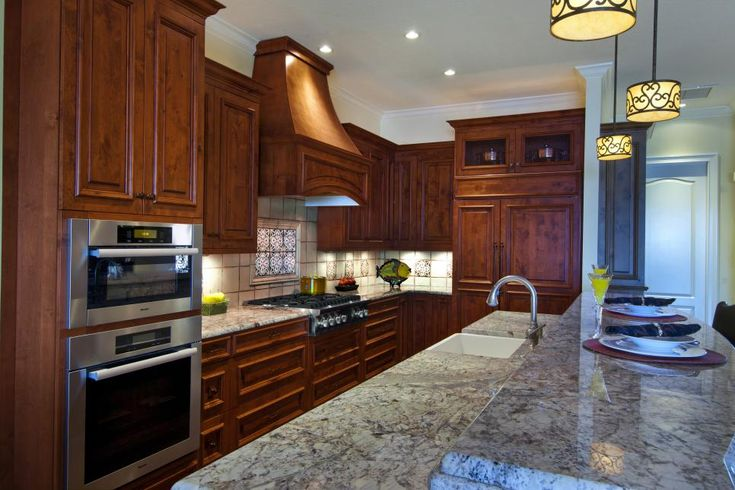 Rich brown cabinetry lends warmth and elegance to this traditional kitchen. A two-tier island provides prep and dining space, and three small pendant lights complete the classic look.