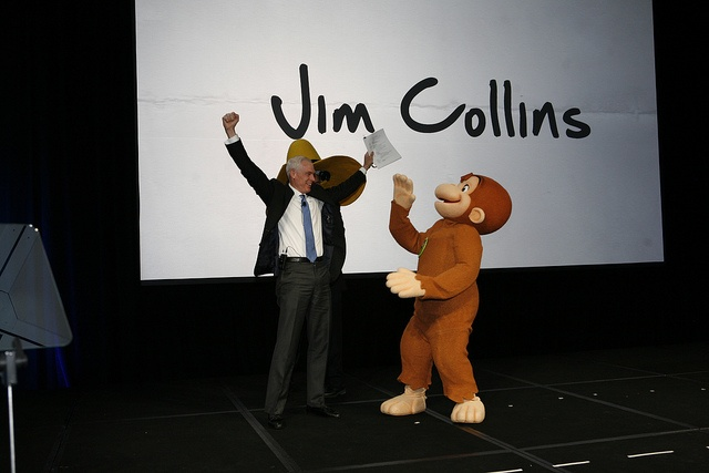Keynote speaker Jim Collins & Curious George monkey around on stage.
