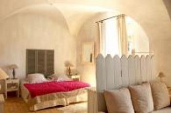 Tomettes anciennes au sol, voûtes d'origine au plafond, tête de lit en persiennes et banquette avec palissade en bois peint composent une décoration pleine de poésie.