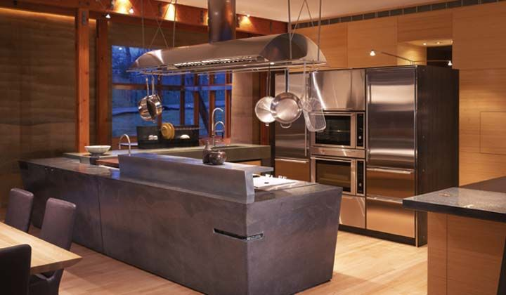This kitchen is located within a massive, 12,000 sq. ft. rammed earth home anchoring a working Napa County, California vineyard. Commissioned to create a sculptural yet functional cooking space expressing art and utility, the design approach was to create a monolith — a unified kitchen space of simple low walls and countertops, seamless cabinetry details and hardware, and a clever orchestration of gourmet appliances to echo the mass of the house and anchor the overwhelming space.