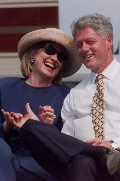 President Clinton and his wife Hillary Rodham Clinton hold hands and laugh during Vice President Al Gore's speech Friday, Aug. 30, 1996, in Cape Girardeau, Mo. | AP Photo