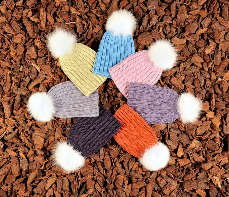 Knitted children's beanies in various colors with fur tassels. Natural materials and handmade in Denmark.