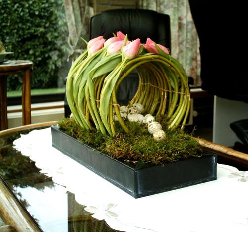 Round floral arangement - sinking rectangular tray filled with moss - a tunnel of smooth branches of for example cornus - there over the tulips or Callas - finish with Easter eggs for Easter