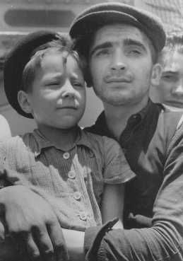 "Eight-year-old Yisrael Meir (Lulek) Lau is held by a fellow Buchenwald survivor, Elazar Schiff, as they arrive in Palestine aboard the RMS ""Mataroa."" Haifa, Palestine, July 15, 1945."
