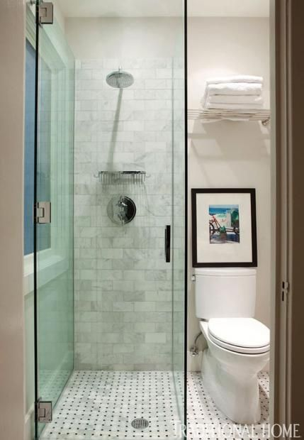 The master bathroom's walk-in shower bears a sleek, slim profile that maximizes the tiny space