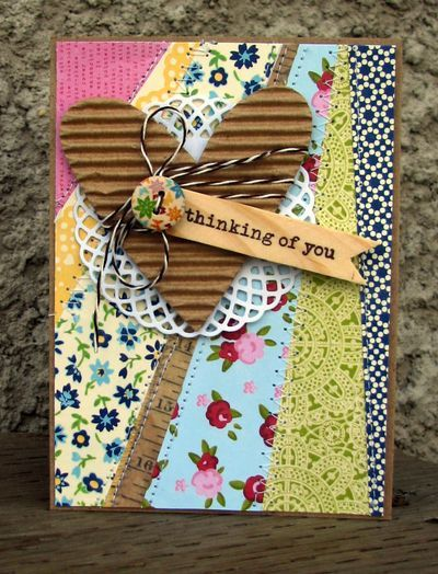 great use of scraps; strip of measuring tape; panel on kraft base with kraft corrugated heart on top of doily. balsa wood sentiment banner; vintage pattern button with twine wrapped around heart; Nicole Nowosad