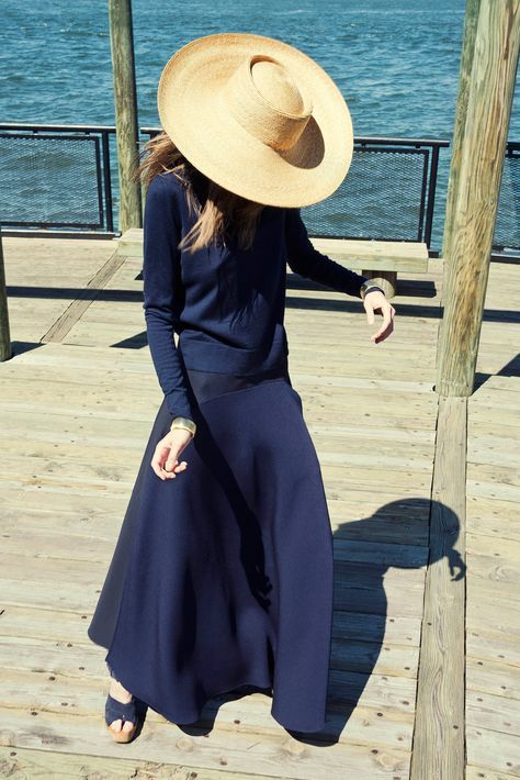 Oversized straw hat, navy blue knit, navy blue silk skirt, and navy blue sandals