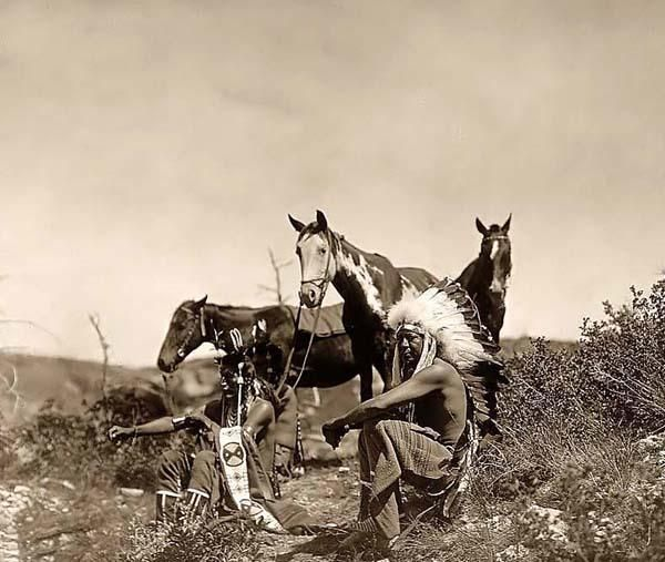 Here for your perusal is a collectible photograph of Indians Talking. It was created in 1905 by Edward S. Curtis.    The photograph illustrates Three Crow men, seated in rocky area with low growing shrubs. Their horses are standing in the background.
